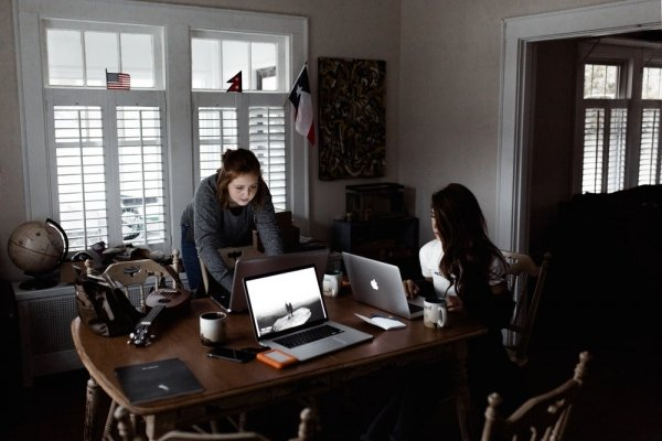 Two young women working at their laptops at a dining table at home