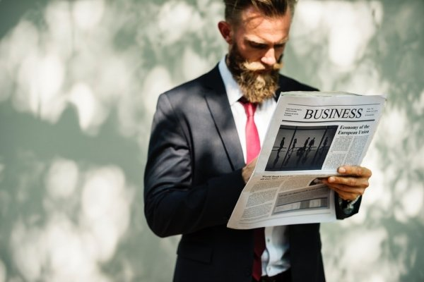 A bearded man in a suit reading the business section of a newspaper.
