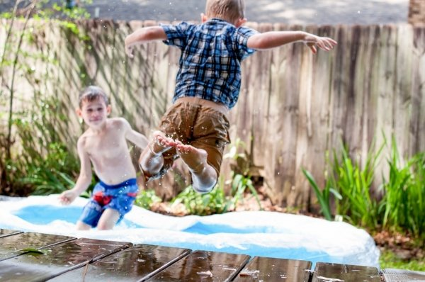 Clothed child jumping from a wooden platform into an inflatable pool where another child is playing