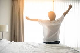 Man wake up and stretching in morning with sunlight | Premium Photo