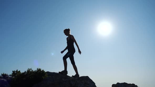 Young Woman Walks Uphill Towards the Summit in Slow Motion. Silhouette of a  Lady Hiking in Beautiful by jm_video